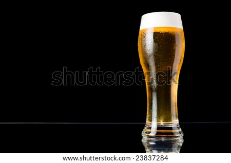 Glass of cold beer with water drops on black background - stock photo