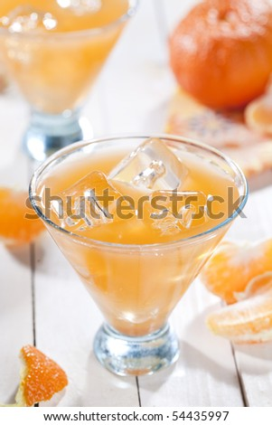 Glass of cold beverage with tangerines - stock photo