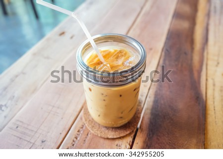 Glass of cold coffee on brown wood table at cafe. - stock photo