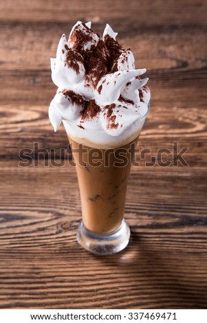 Glass Of Cold Coffee With Whipped Cream On Wood - stock photo