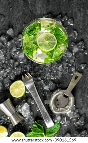 Glass of cold drink with lime, mint, ice. Tonic water, cocktail, mojito, caipirinha. Top view - stock photo