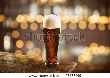 Glass of cold fresh beer on table, on dark pub background - stock photo