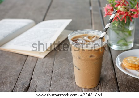 Glass of Cold Iced Coffee put on old wood table. - stock photo