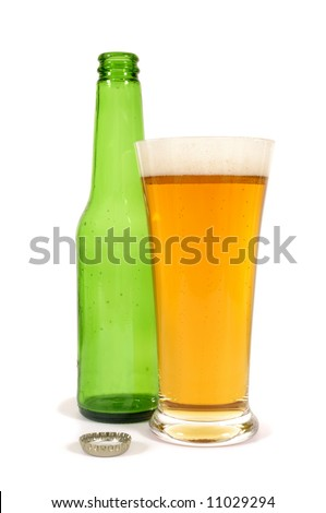 Glass of cold lager beer with empty green bottle isolated on white background, vertical