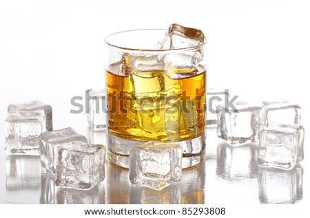 Glass of cold whiskey with ice isolated over white - stock photo