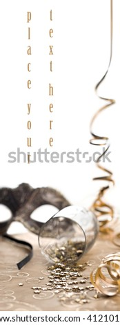 glass of confetti with mask and serpentine - stock photo