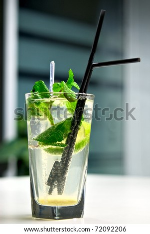 Glass of cool mojito cocktail on a white table with a background of interior cafe - stock photo