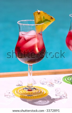 Glass of cranberry alcohol cocktail on swimming pool side
