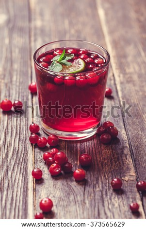 Glass of cranberry juice with mint on wooden table - stock photo