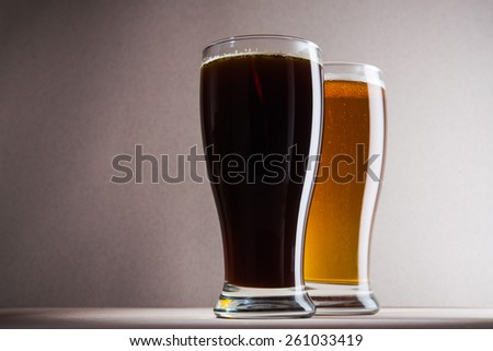 Glass of dark beer on background