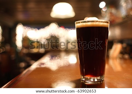 Glass of dark beer on the counter.