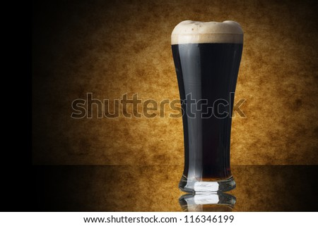 Glass of dark beer on yellow background