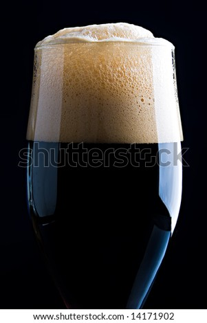 Glass of dark beer with beautiful foam close up - stock photo
