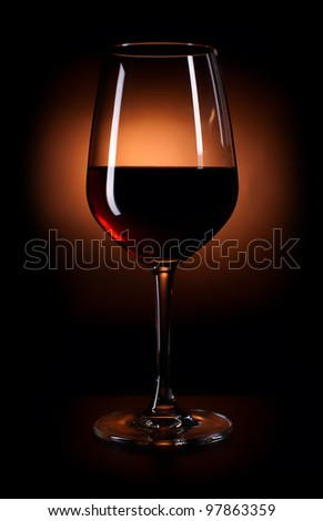 Glass of dark red wine on the black background - stock photo