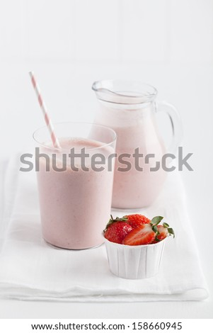 Glass of delicious strawberry smoothie with pink straw served on white linen on top of white table with a pitcher and cup of fresh strawberries.