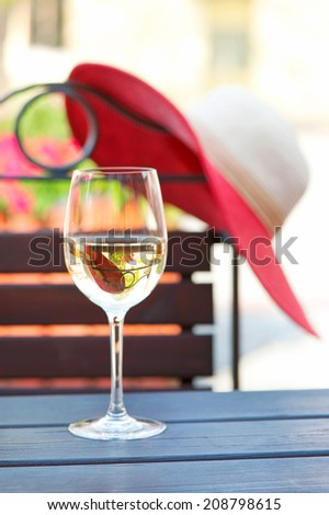 Glass of delicious white wine on wooden table in summer restaurant. Outdoors. - stock photo