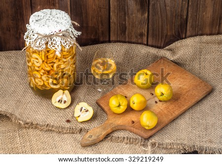 Glass of drink and jar of alcohol tincture with quince fruits. - stock photo