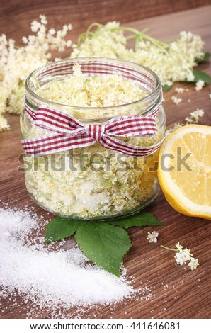 Glass of elderberry flowers and ingredients for preparing healthy juice on rustic board, alternative medicine and therapy - stock photo