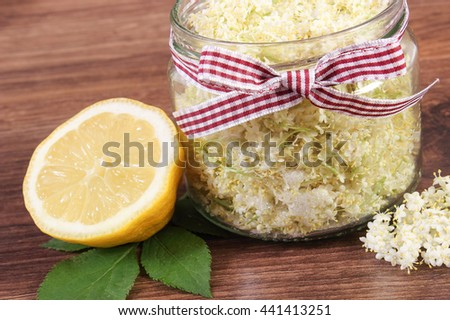 Glass of elderberry flowers and lemon for preparing healthy juice on rustic board, alternative medicine and therapy - stock photo