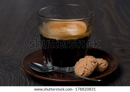 glass of espresso and almond cookies on dark background, close-up - stock photo