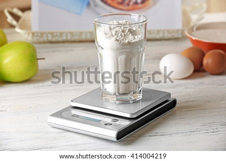 Glass of flour and digital kitchen scales on light wooden table - stock photo