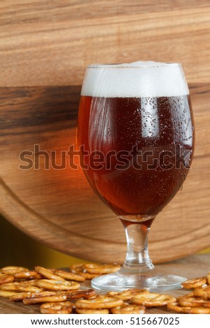 Glass of foamy beer alcohol with german pretzel. Traditional bavarian Oktoberfest snacks and drink in bar on wooden background