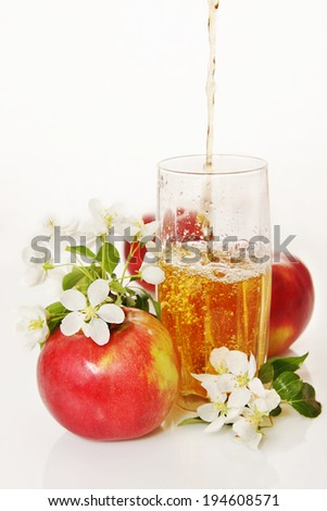 Glass of fresh apple juice with ripe red apples and blooming flowers - stock photo