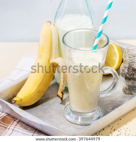 Glass of fresh Banana smoothie with cocktail tube, served with bottle of milk, open banana, jar of chia seeds and lemon on aluminum tray over white wooden table. Square image with selective focus - stock photo