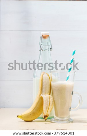 Glass of fresh Banana smoothie with retro cocktail tube, served with bottle of milk and open banana over white wooden table. Rustic style - stock photo