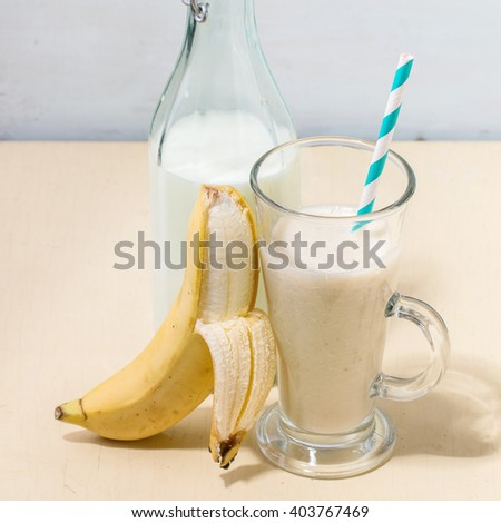 Glass of fresh Banana smoothie with retro cocktail tube, served with bottle of milk and open banana over white wooden table. Square image with selective focus - stock photo