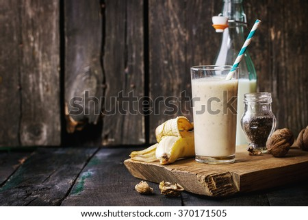 Glass of fresh Banana smoothie with retro cocktail tube, served with bottle of milk, open banana, chia seeds and walnuts on wooden chopping board over wooden table. Rustic style, retro filter effect - stock photo