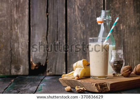 Glass of fresh Banana smoothie with retro cocktail tube, served with bottle of milk, open banana, chia seeds and walnuts on wooden chopping board over dark wooden table. Rustic style - stock photo