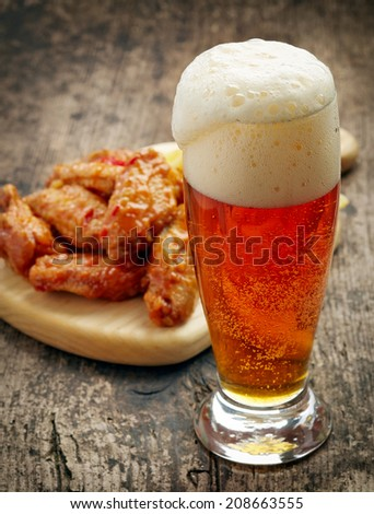 glass of fresh beer and fried chicken wings on wooden table - stock photo