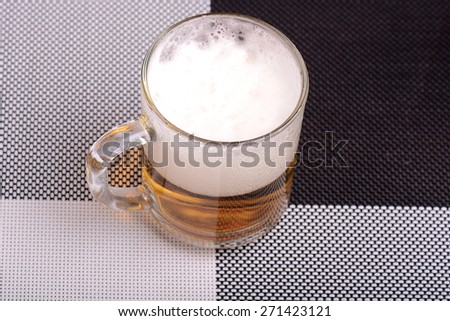 Glass of fresh beer with cap of foam - stock photo