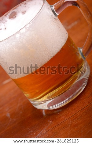 Glass of fresh beer with cap of foam on wooden plate - stock photo