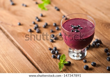 Glass of fresh blueberry smoothie with blueberries - stock photo
