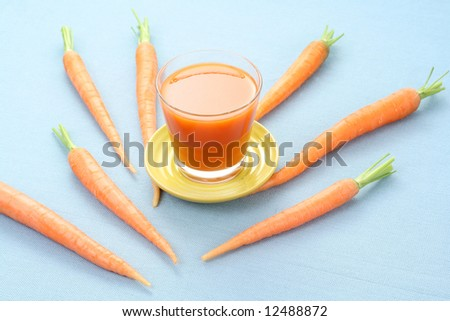 glass of fresh carrot juice and some fresh vegetables