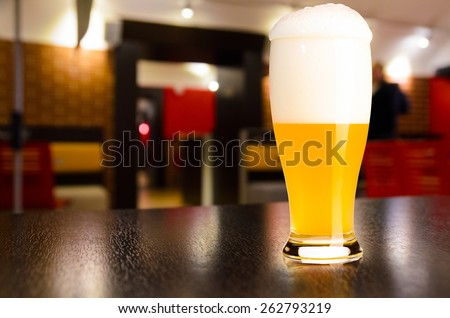 glass of fresh draft weiss beer on table in pub - stock photo