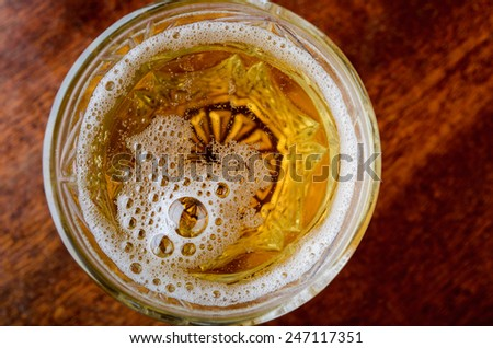 glass of fresh lager beer on dark wooden table - stock photo