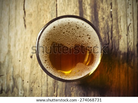 glass of fresh lager beer on wooden table - stock photo