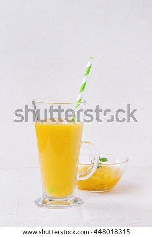 Glass of fresh mango smoothie with striped green cocktail tube, and mango dessert with mint, served over white linen tablecloth with white textured background. With space for text - stock photo