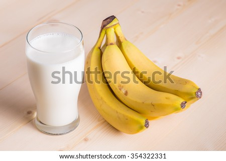 Glass of fresh  milk and banana on wooden background - stock photo