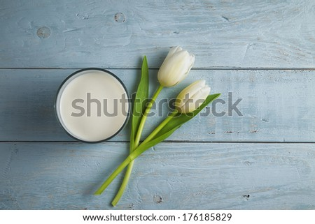 glass of fresh milk and tulips on old wooden table - stock photo