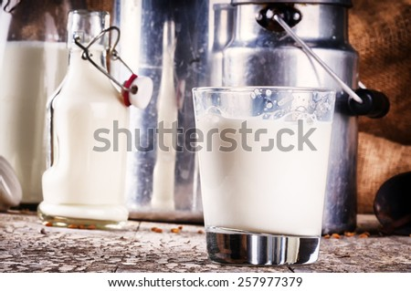 Glass of fresh milk in country setting - stock photo