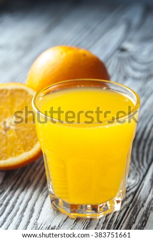 Glass of fresh orange juice and ripe oranges on wooden table. Focus on glass.