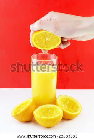 Glass of fresh orange juice with hand,which squeeze of orange.  On red-white  background.