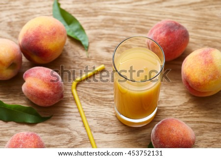 Glass of fresh peach juice and ripe fruits