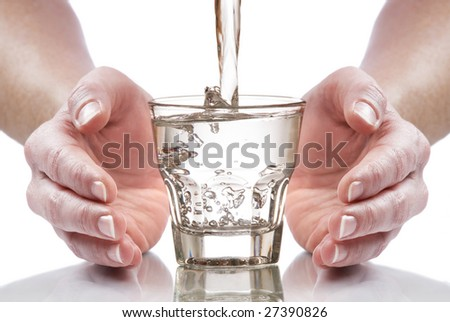 glass of fresh water between hands close up - stock photo