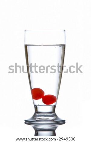 Glass of fresh water with cherries reflected on white background - stock photo