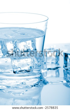 Glass of fresh water with cubes of ice in it over paper background - stock photo